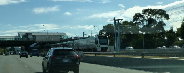 A commuter train in the middle of the freeway in Perth